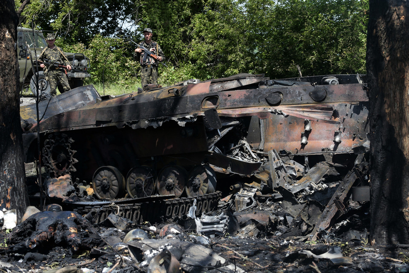 Ukrainian soldiers stand on a road behind charred tank near the